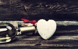 Coeur, cadeaux et bouteille de vin sur le Tableau Image stock