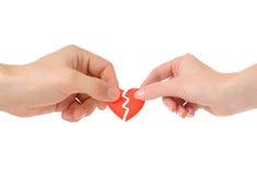 Coeur cassé dans des mains mâles et femelles Photographie stock