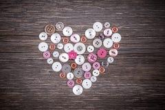 Coeur coloré de boutons sur le vieux fond en bois Photos stock