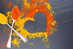 Coeur coloré des épices sur le fond noir avec deux cuillères de vintage Suggestion du concept de jour de valentines Images libres de droits