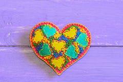 Coeur créatif de feutre pour le jour de valentines Cadeau brodé de coeur sur le fond en bois pourpre avec l'espace de copie pour  Image stock