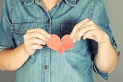 Coeur déchiré chez des mains des femmes Image stock