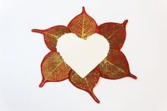Coeur déchiré de livre blanc entouré par le rouge et les feuilles de papier d'or Photo stock