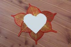 Coeur déchiré de livre blanc entouré par le rouge et les feuilles de papier d'or sur le fond en bois Image stock