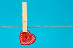 Coeur décoratif arrêté sur la corde à linge Photographie stock libre de droits