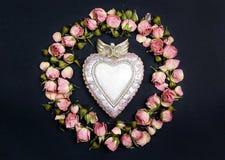 Coeur décoratif avec le cadre rond de petites roses sèches sur le fond noir Place pour le texte Photos libres de droits
