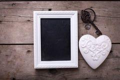 Coeur décoratif blanc, tableau noir vide et clé de vintage sur l'AG Images libres de droits