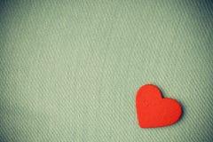 Coeur décoratif en bois rouge sur le fond gris de tissu. Image stock