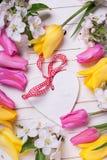 Coeur décoratif, fleurs de pommier et tulipes lumineuses sur le petit morceau Photo libre de droits