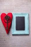 Coeur décoratif rouge, clé de vintage et tableau noir vide sur l'ardoise Photos libres de droits