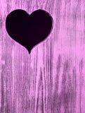 Coeur découpé dans un conseil en bois Fond Photographie stock