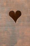 Coeur découpé sur un conseil en bois Photos libres de droits