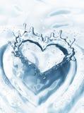 Coeur d'éclaboussure de l'eau avec des bulles sur le fond de l'eau bleue Photographie stock libre de droits