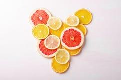 Coeur d'agrumes des tranches de citron, orange, pamplemousse sur le fond blanc Amour, sain, concept d'écologie Image libre de droits