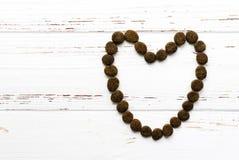 Coeur d'aliments pour chiens sur la table en bois de vintage Images stock