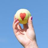 Coeur d'amour de balle de tennis - tenu par la femme Photo stock