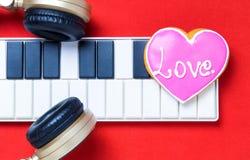 Coeur d'amour de clavier du Midi d'écouteur de musique sur le fond rouge Photo libre de droits