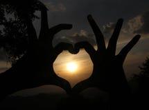Coeur d'amour des mains avant coucher du soleil Photos libres de droits