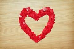 Coeur d'amour fait avec les confettis en forme de coeur Photographie stock libre de droits