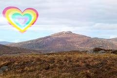 Coeur d'arc-en-ciel au-dessus d'un paysage montagneux photo libre de droits