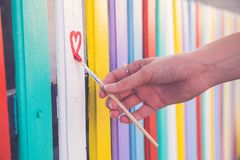 Coeur d'aspiration de femme sur la barrière colorée avec la brosse de peinture Images libres de droits
