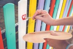 Coeur d'aspiration de femme sur la barrière colorée avec la brosse de peinture Photographie stock