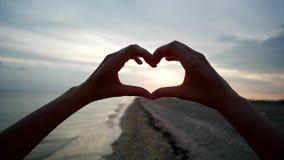 Coeur d'exposition de mains au coucher du soleil clips vidéos