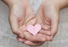 Coeur d'origami dans des mains humaines Image stock