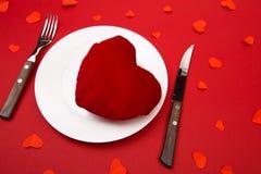 Coeur d'un plat pour le dîner Une soirée romantique avec des coeurs sur le fond rouge images stock