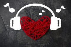 Coeur dans des écouteurs sur un fond foncé Thème pour le jour du ` s de Valentine Mariage, amour Images stock