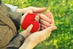 Coeur dans des mains d'enfant et de mère Photo stock