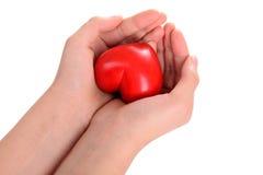 Coeur dans des mains humaines Image stock
