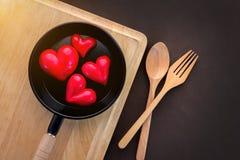 Coeur dans la casserole avec la cuillère et la fourchette en bois Images libres de droits