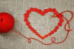 Coeur dans la forme des boutons rouges, du pointeau et du fil photo libre de droits