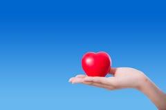 Coeur dans la main sur le fond de ciel Photo stock