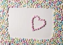 Coeur dans le cadre de mini guimauves colorées sur le fond blanc Vue supérieure Images stock