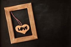 Coeur dans le cadre de tableau en bois sur le tableau Image libre de droits
