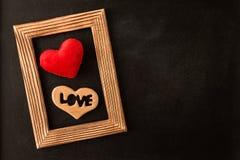 Coeur dans le cadre de tableau en bois sur le tableau Photo stock