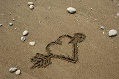 Coeur dans le sable avec une flèche Images libres de droits