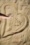 Coeur dans le sable et la main de l'enfant Image stock