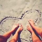 Coeur dans le sable sur la plage avec des pieds Image libre de droits