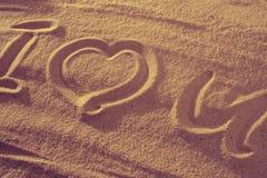 Coeur dans le sable sur la plage Symboll d'amour avec le texte Photos stock