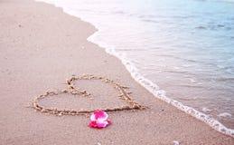 Coeur dans le sable sur le bord de la mer Photos stock