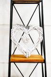 Coeur dans un appui vertical décoratif de coeur se tenant sur le métal et la position en bois contre le mur blanc Photo stock