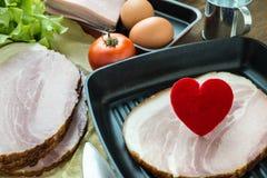 Coeur dans une poêle pour le concept à cuire sain d'amour ou de coeur Image libre de droits