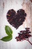 Coeur de baie de sureau fraîche sur le vieux fond en bois, symbole de l'amour Photo libre de droits