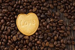 Coeur de biscuit avec l'amour de mot sur le fond de haricots Images stock