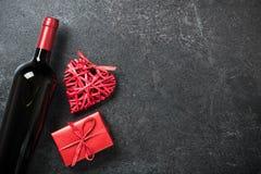 Coeur de bouteille, de boîte-cadeau et d'osier de vin rouge sur le fond noir Photos libres de droits