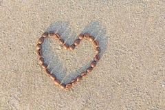 Coeur de café Des grains du café sont présentés sur le sable en FO Image libre de droits