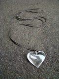 Coeur de collier sur le sable Photographie stock libre de droits